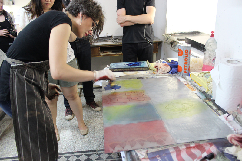 woman making a prints in studio with students watching