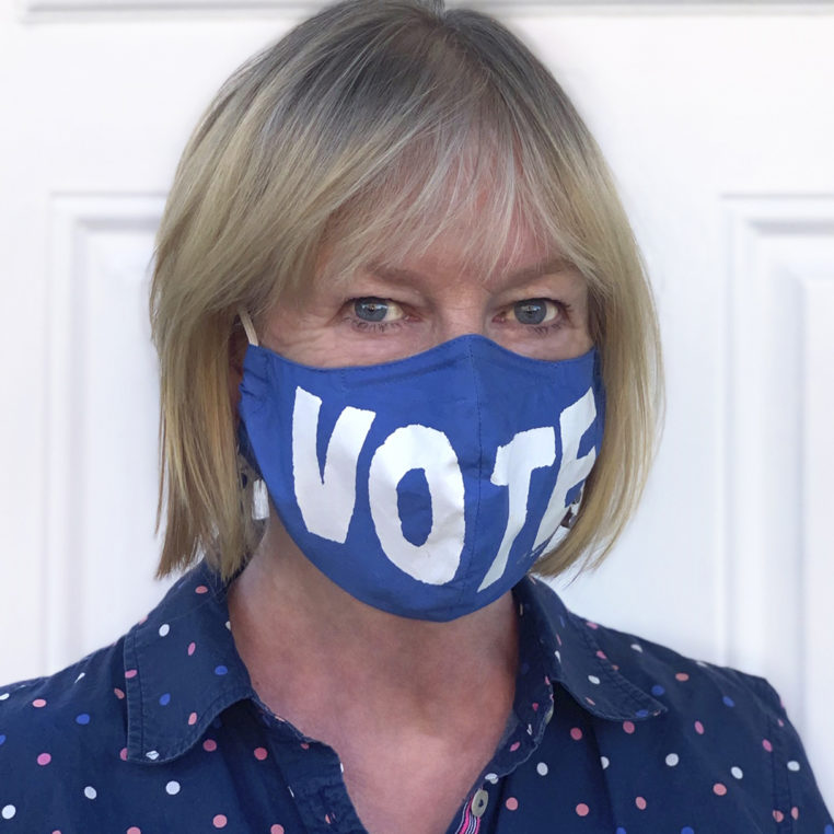 Headshot of Deborah Hussey wearing a blue facemask with the work vote on it