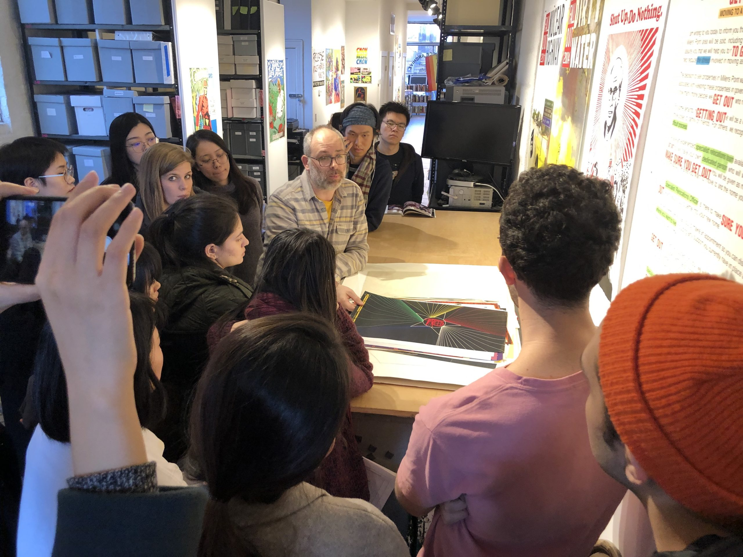 Josh MacPhhee and students looking at poster designs
