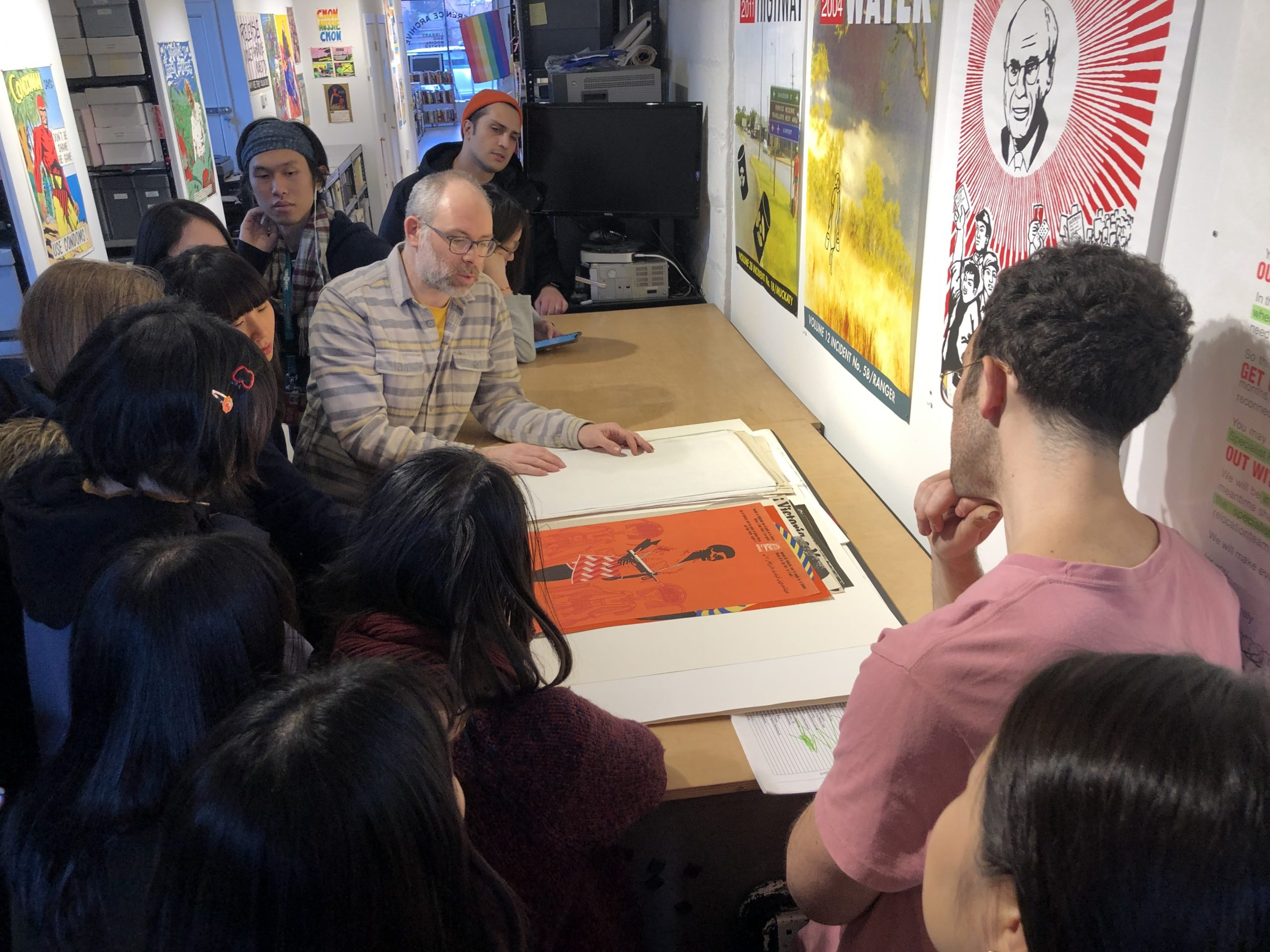 Josh MacPhhee showing posters to students