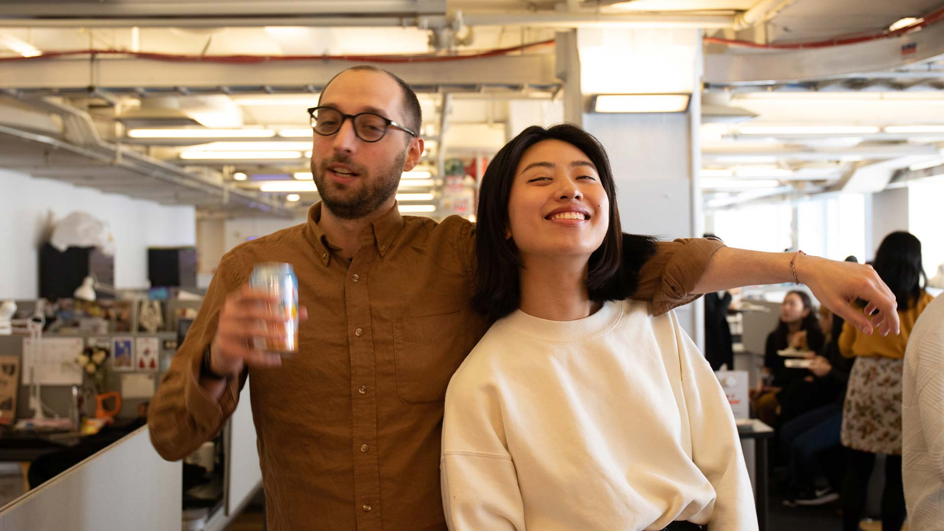 two students posing while holding sparkling water