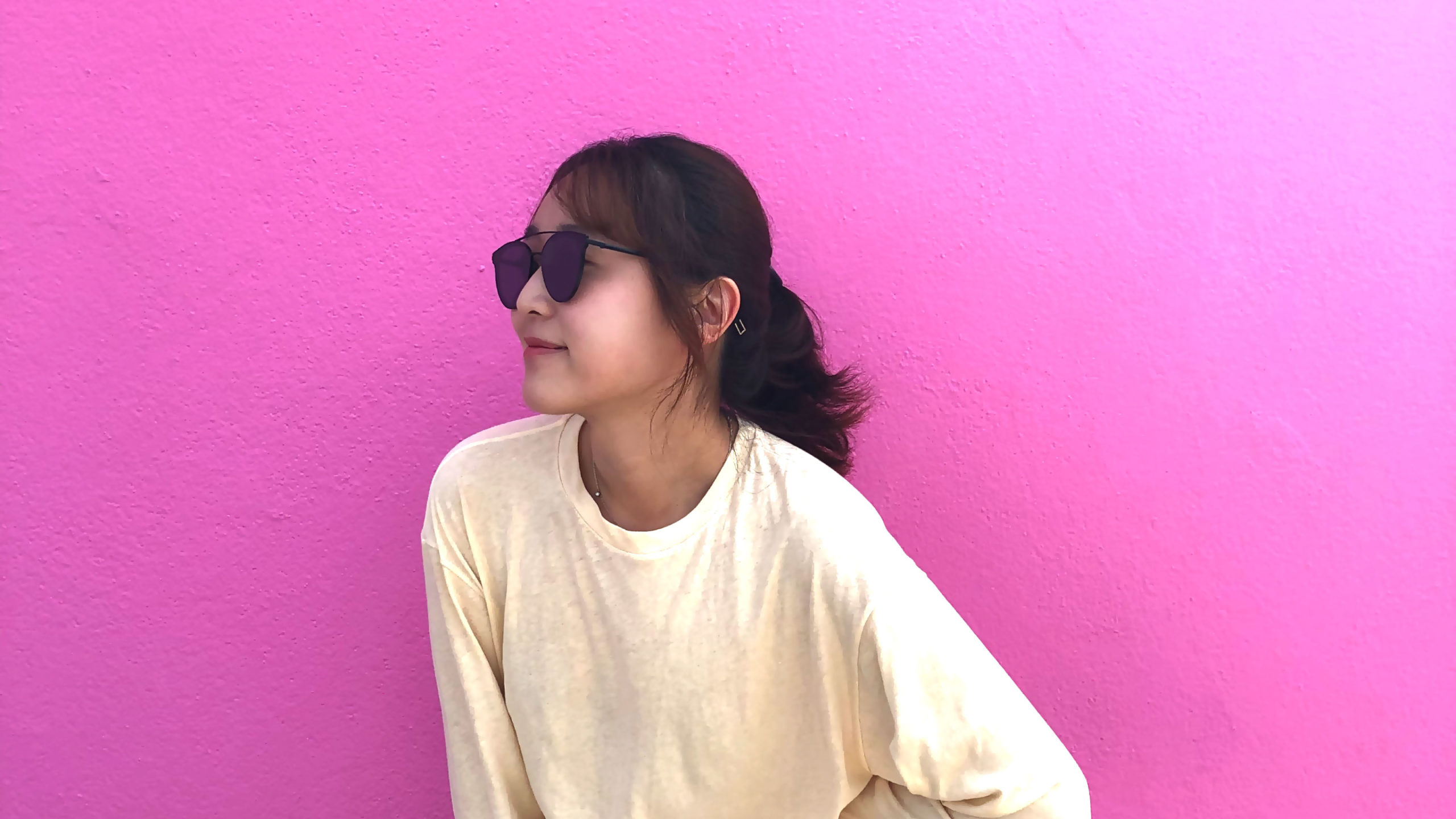 picture of Mingu Lee posing in beige long sleeve and glasses in front on pink wall