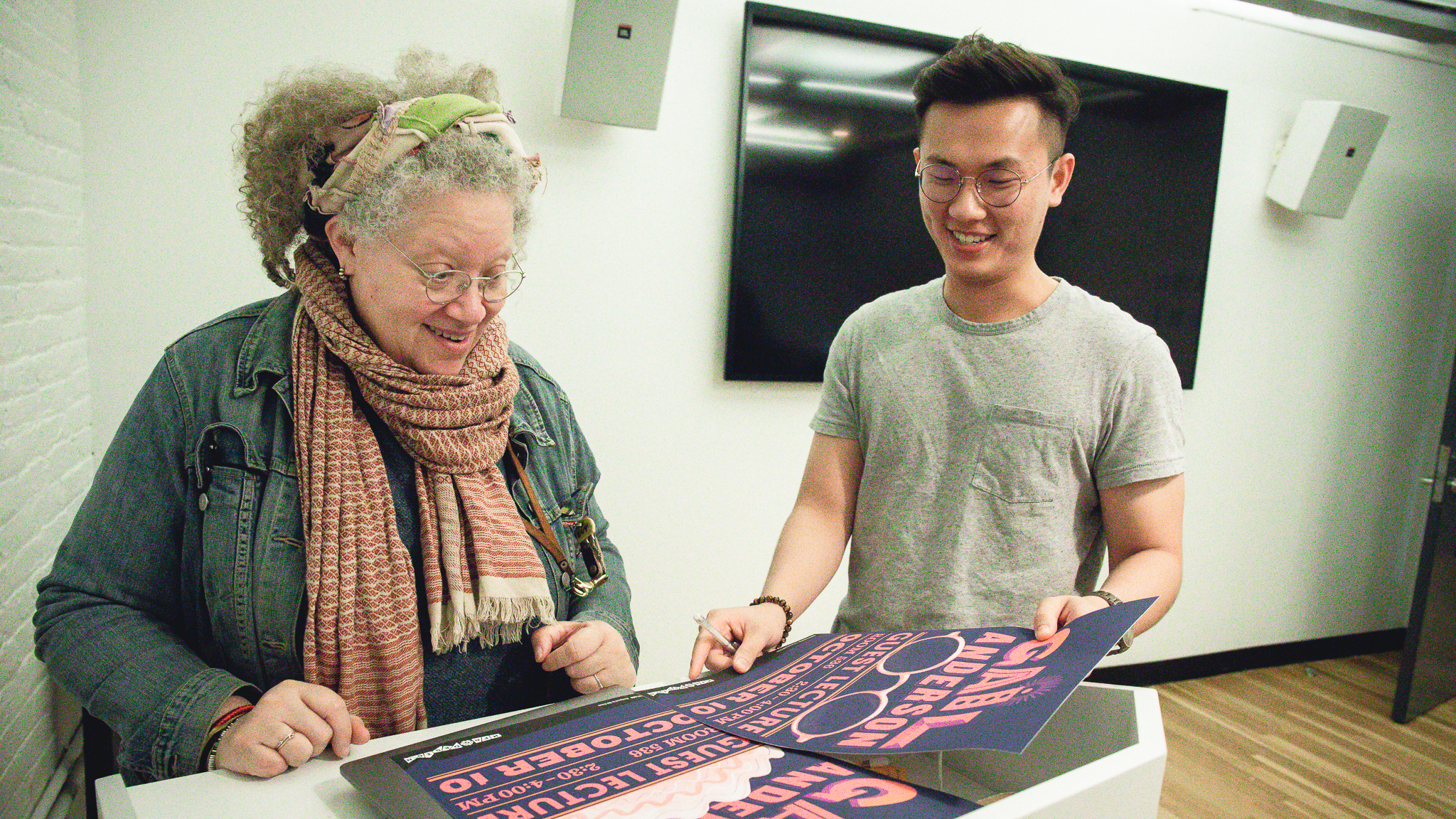 Bill Chien showing poster he designed for Gail Anderson's guest lecture