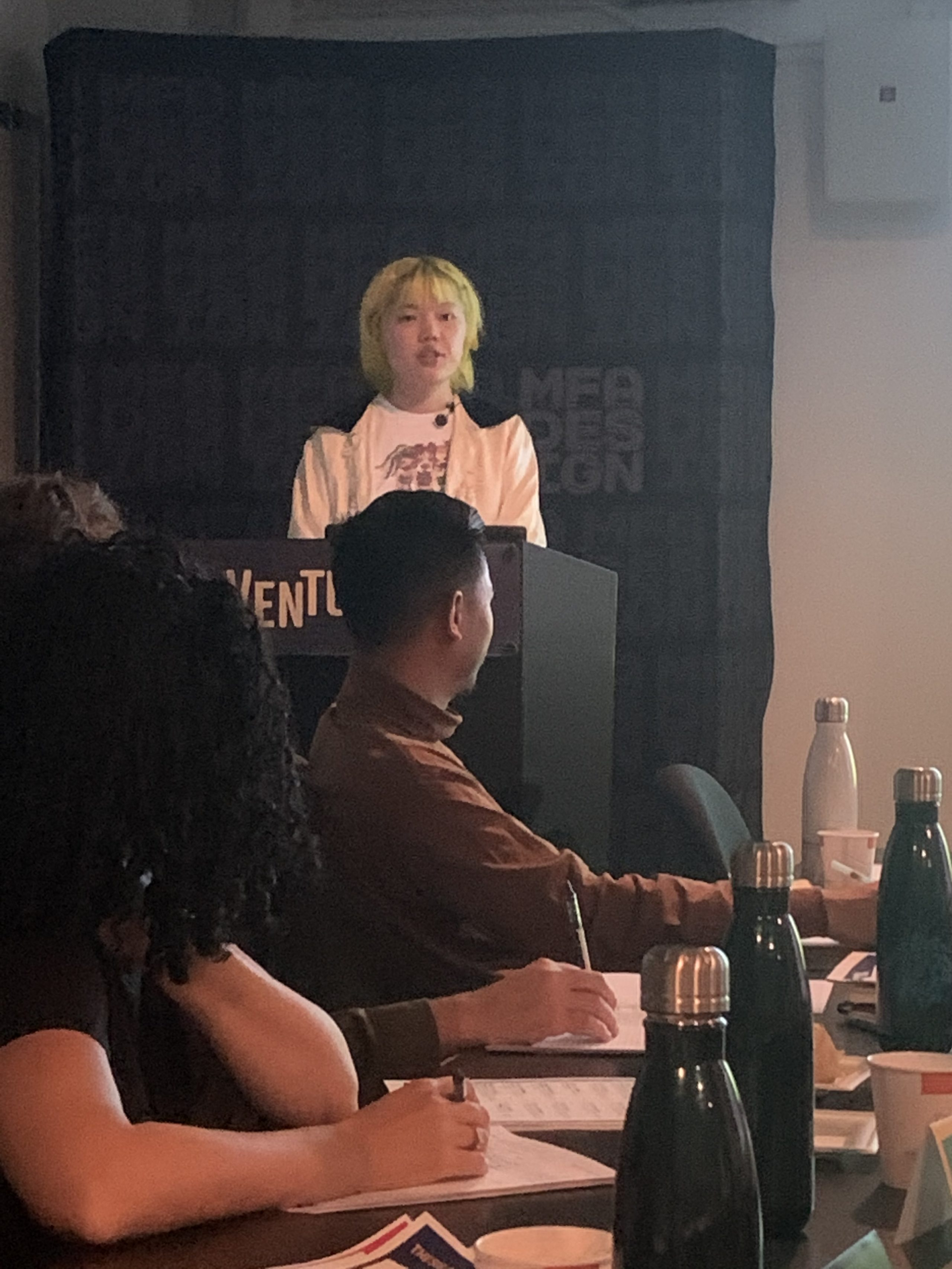 girl with green hair presenting to people