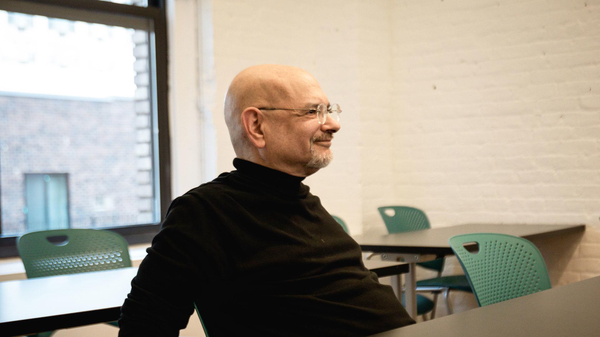 Steven Heller weaning glasses and black turtleneck, smiling in MFAD classroom