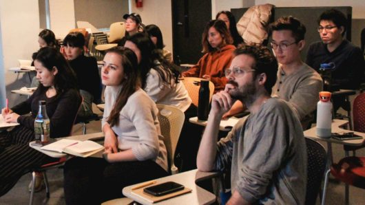 Students at SVA MFA Design watching a lecture in a darkened classroom