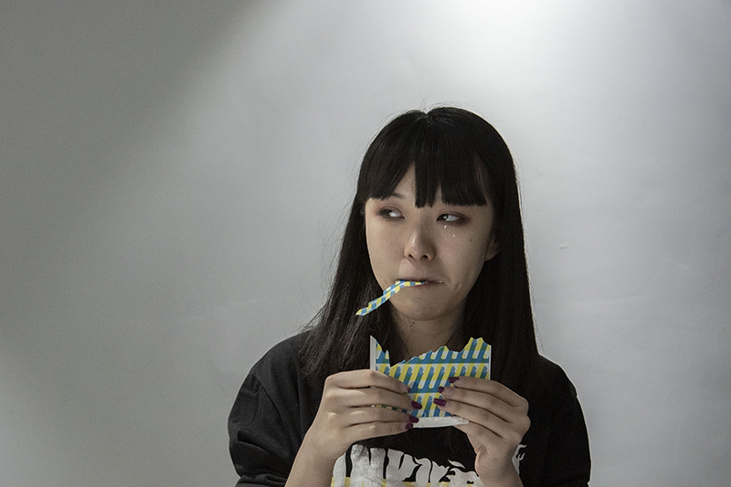 Miao Zhao eating printed paper