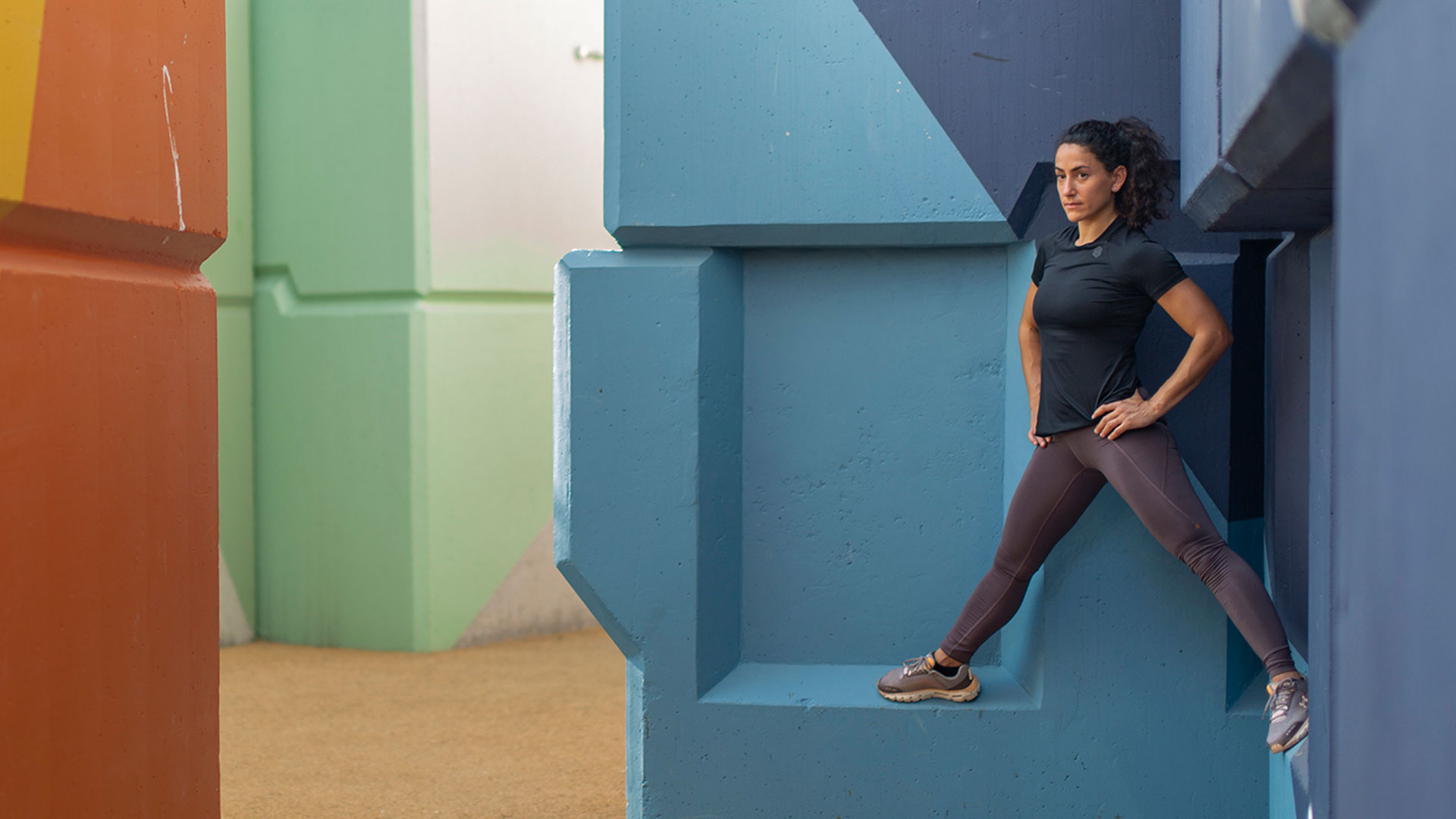 Samia Kallidis in tight workout clothes on a colorful geometric sculpture