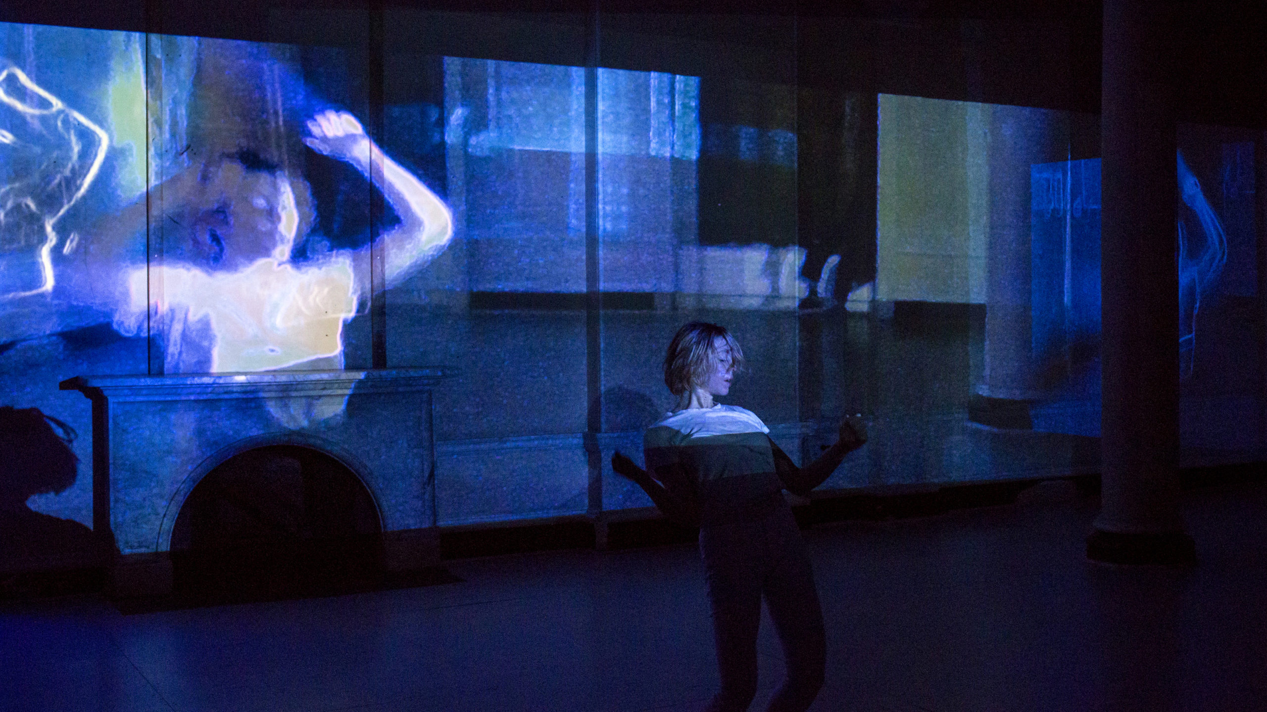 woman standing and leaning backwards on a stage in front of a blue projection of a woman