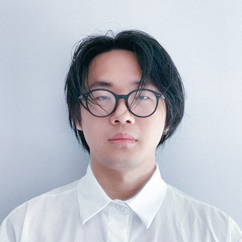 Shukang Yu in white button up shirt and round, dark frame glasses