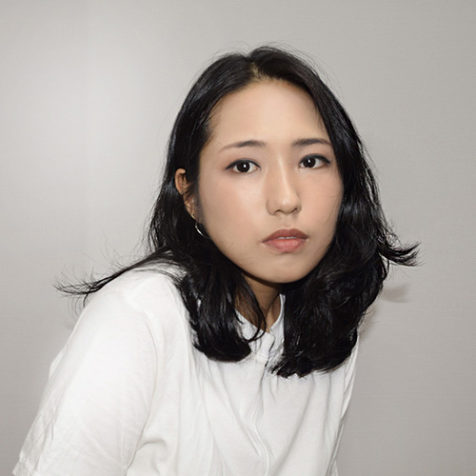 Sue Kim portrait with white shirt light grey background