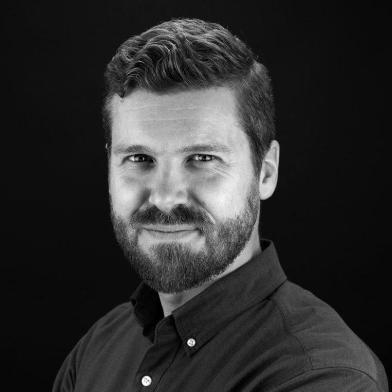 tim cohan portrait in dark shirt and dark background