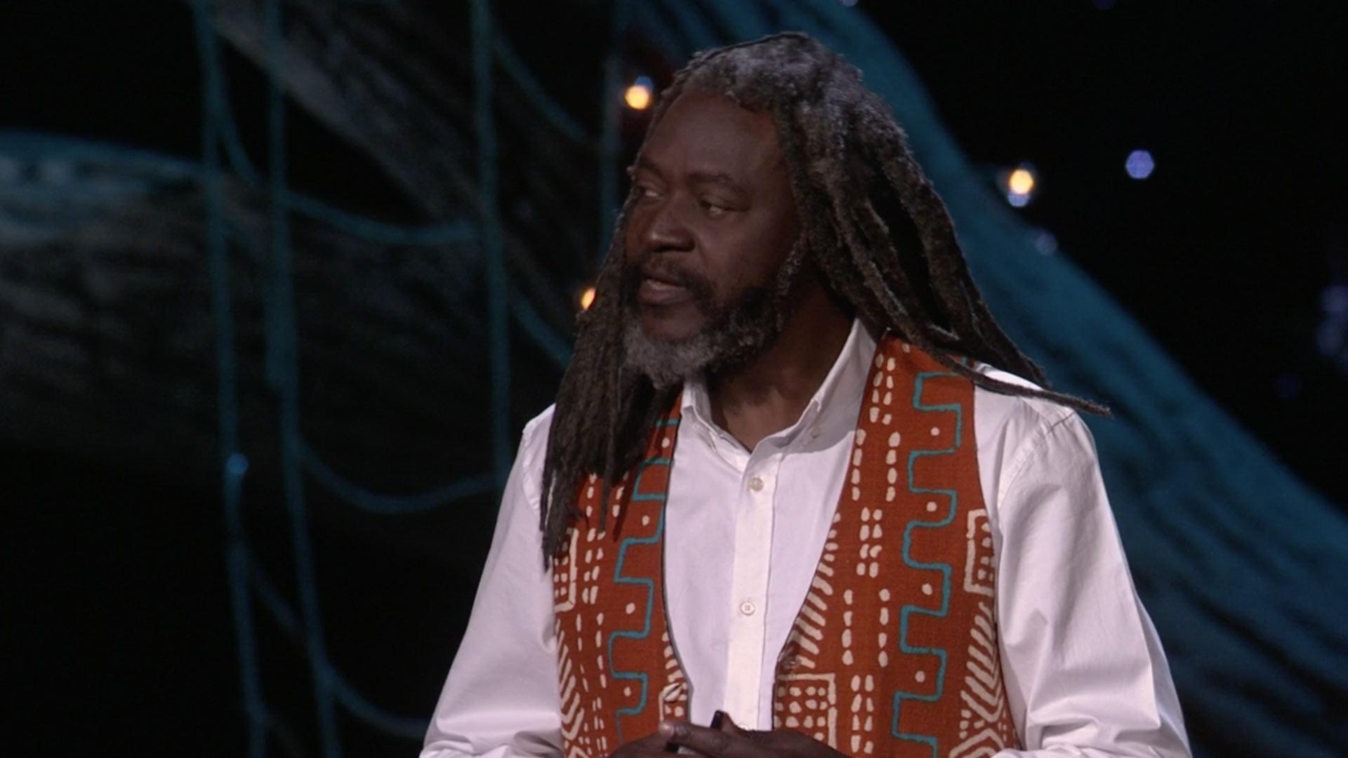 screen shot of Saki Mafundikwa on white shirt ans affican style vest