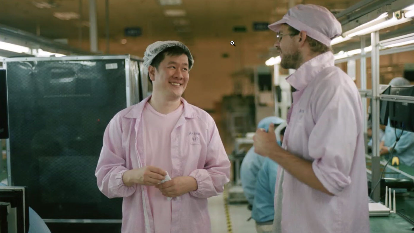 hugh francis and another man dressed in pink uniforms in phone factory